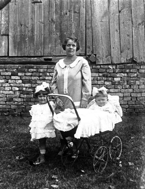 Kobieta z dziewczynk¹ i dzieckiem w wózku.